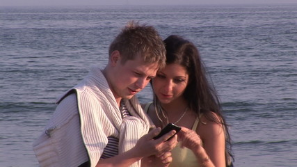 young couple with cellphone during honeymoon