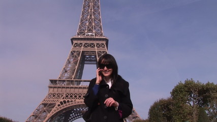 Attractive woman on the phone in front of the Eiffel tower