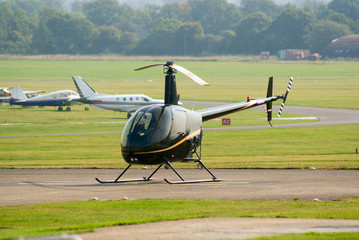 Black Robinson R-22 helicopter in the parking