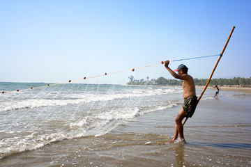 Fishermen collecting ther catch from sea on the beach in Asvem