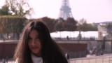 Young hispanic woman smiling with the Eiffel tower in background