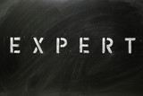 The word EXPERT in stencil letters on a blackboard poster