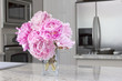 vase of pink peonies in modern kitchen
