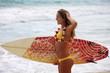 teenage girl in yellow bikini with surfboard at a hawaii beach