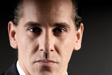 Adult businessman closeup portrait on dark background.