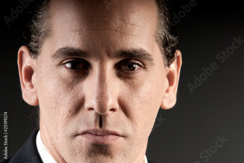 Adult businessman closeup portrait on dark background.