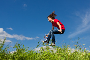 Girl jumping, running against blue sky