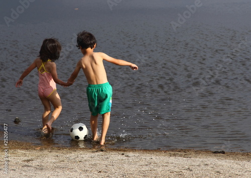 Young Boy and Girl Playing with Ball on Beach