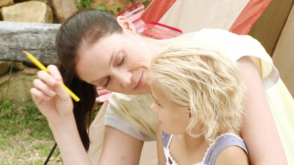 mother writing with her cute daughter in the garden
