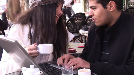 hispanic couple working on laptop in a cafe