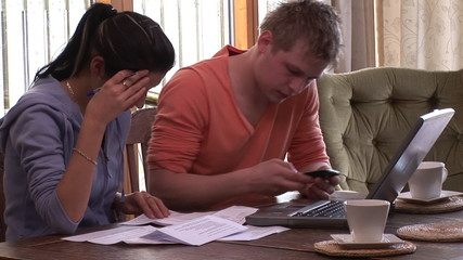 young couple with bills and laptop at home