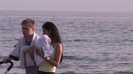 young couple with baby along the sea