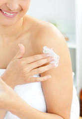 Happy young woman with a towel putting cream on her face in the