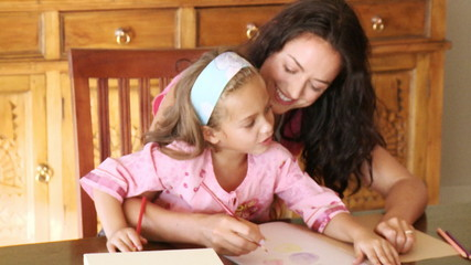 mother painting with her daughter at home