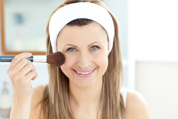 Smiling caucasian woman putting powder on her face smiling at th
