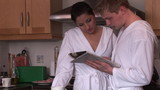 young couple with bathrobes reading newspaper during breakfast