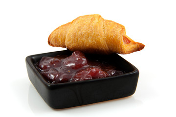 croissant and marmalade over white background