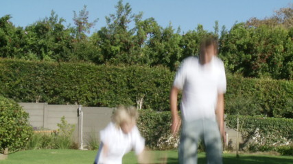energetic father and son jumping on a trampoline in their garden