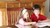 young brother and sister doing homeworks at home