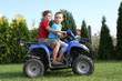 Two young boys driving a quad bike