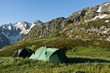 Camping tents on sunny grassland.