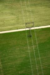 Power line through green fields
