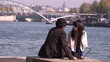 romantic couple sitting along the river Seine