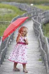 Little blond girl with red umbrella on boardwalk