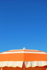 Orange striped beach umbrella on blue sky, Rimini, Italy