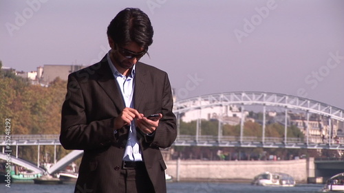 businessman in suit working outdoors with river in background