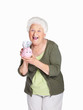 Happy mature woman holding piggy bank isolated against white