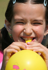Young girl is blowing yellow balloon
