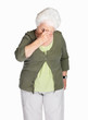 An elderly woman holding her head in pain isolated against white