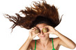 Beautiful woman hold kiwi near eyes hair is dishevelled isolated