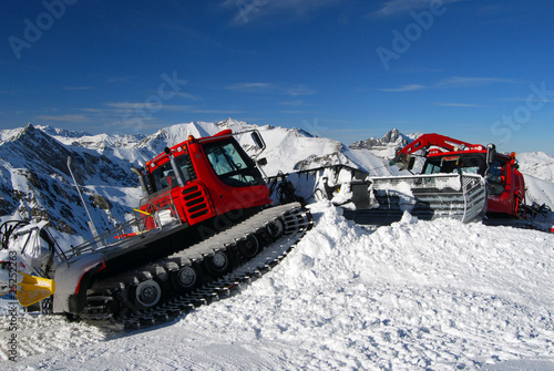 Red snowplows on a slope