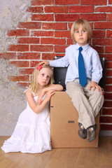 Boy and girl sitting on a cardboard box and a suitcase. Move