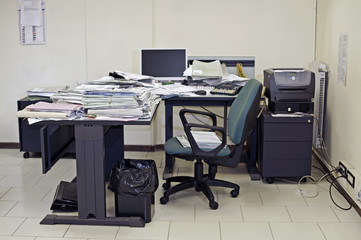 Lonely office room with messy desk filled up with documents