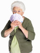 An elderly woman holding currency notes on white background