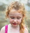 A Little Girl with Ringlets in Her Hair Looking Pensive