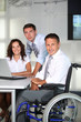 Businessman in wheelchair working in the office with colleagues