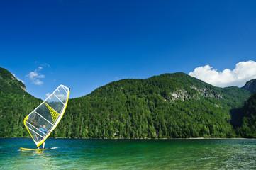 Windsurfer on mountain lake. Copyspace on blue sky.