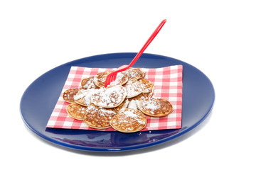 Dutch little pancakes called poffertjes with powdered sugar on a