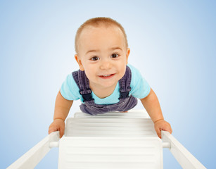 Little boy walking on ladder