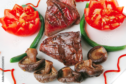 fillet mignon on a white plate and tomatoes