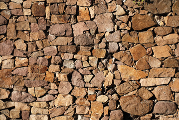 Closeup view of ocre irregular stone wall