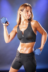 Toned blond working out with dumbbells