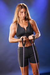 Cute blond in workout gear pulls tension string