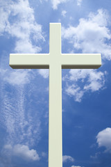 White Christian cross in front of a cloudy sky