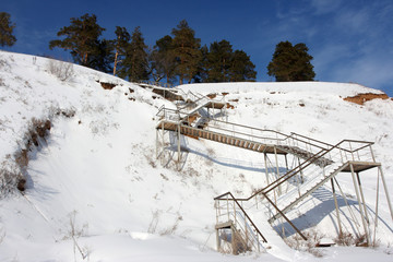 Stairs with landing against a snow slope against pines