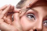 Woman tweezing eyebrow poster